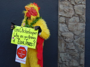 A protester dons a chicken suit at Gov. John Hickenlooper's fundraiser in favor of Prop AA at the Denver Beer Co. in the LoHi neighborhood.